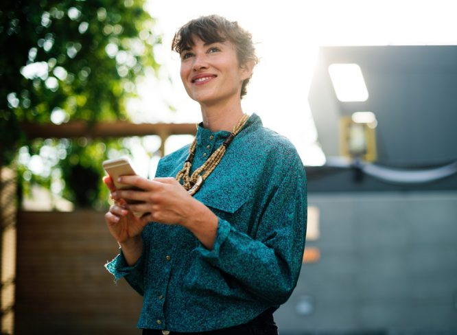 smiling woman in blue dress shirt holding gold iPhone 6 standing in front of house near green leafed tree during daytime